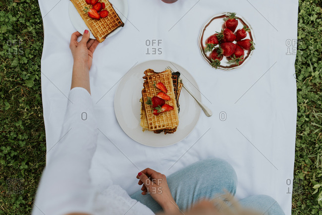 Overhead view of woman eating Belgium waffles with strawberries