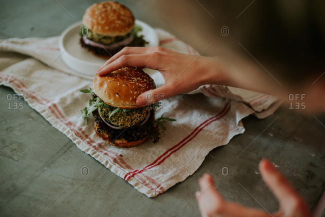 Woman touching a beetroot burger