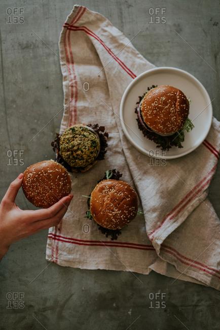 Woman's hands putting bun on a beetroot burger