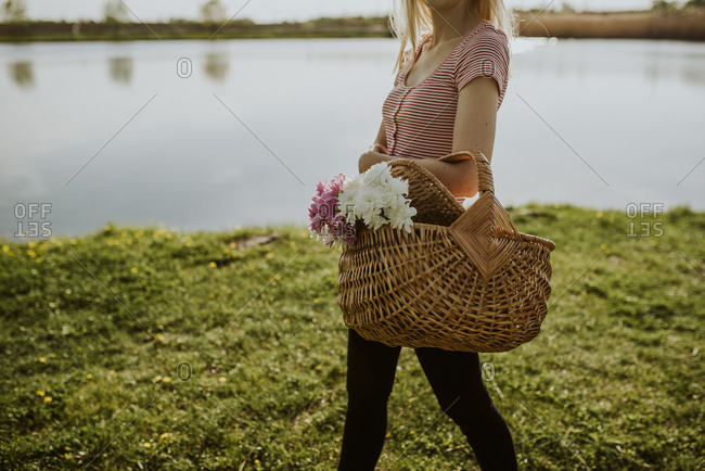 Woman walking beside lake with a picnic basket filled with flowers