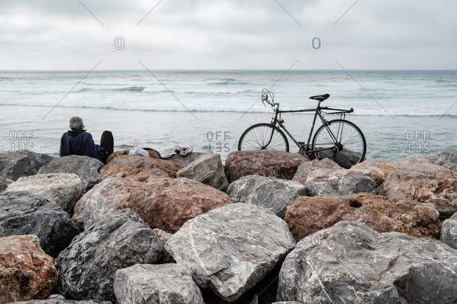 Man with bike on rocky shore