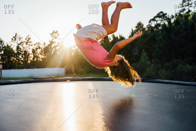 Girl doing a somersault on trampoline