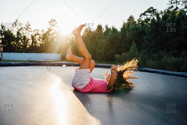 Girl landing on her back after doing a flip on trampoline