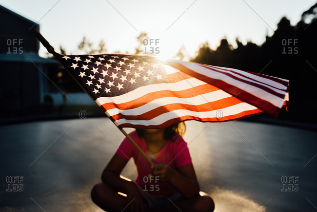 Girl waving American flag in front of her face