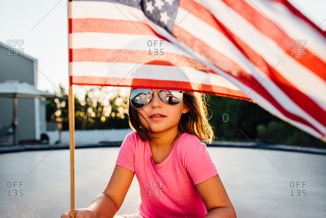 Girl wearing sunglasses holding American flag