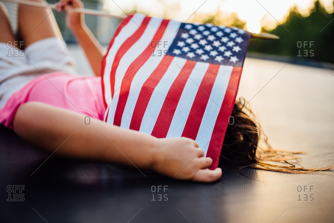Girl covering her face with American flag
