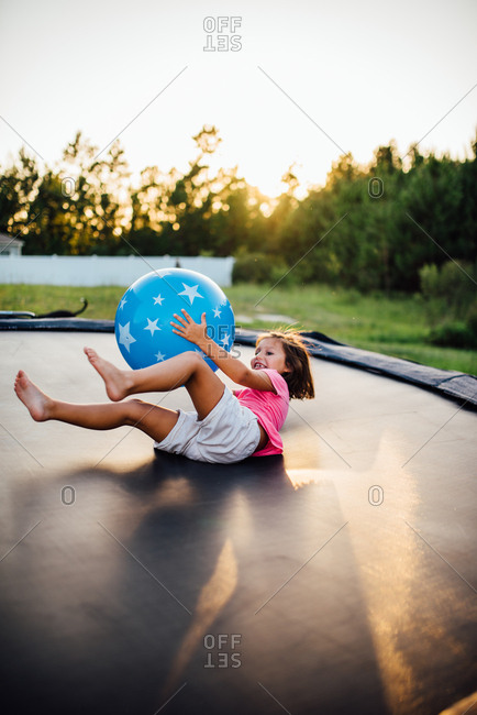 Girl playing with bouncing ball on trampoline