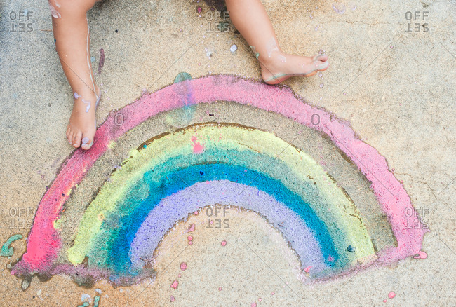 Child's feet by sidewalk chalk rainbow
