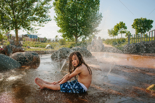 Long-haired boy cooling off at sprayground