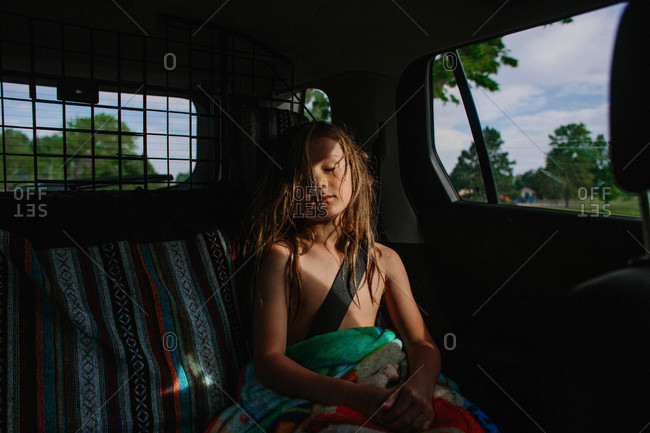 Boy with long hair asleep in back seat