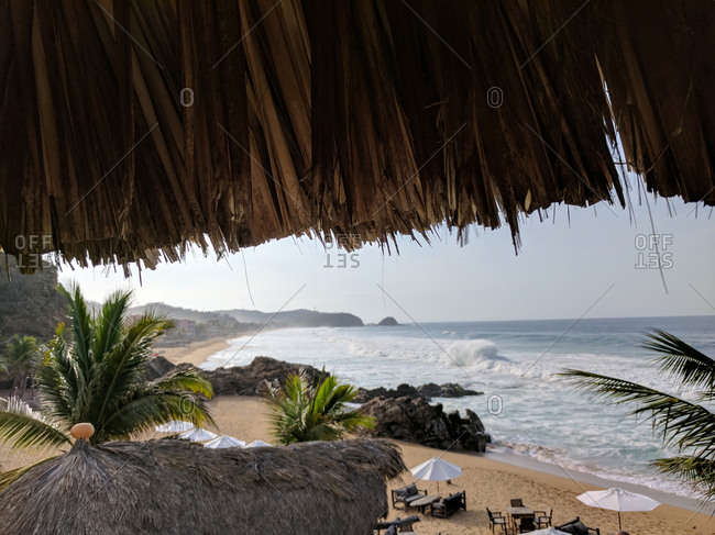 Beach from from under thatched roof