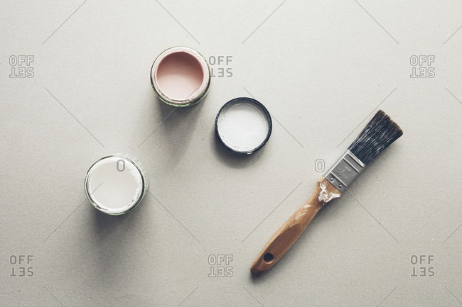Tins of paint and paintbrush