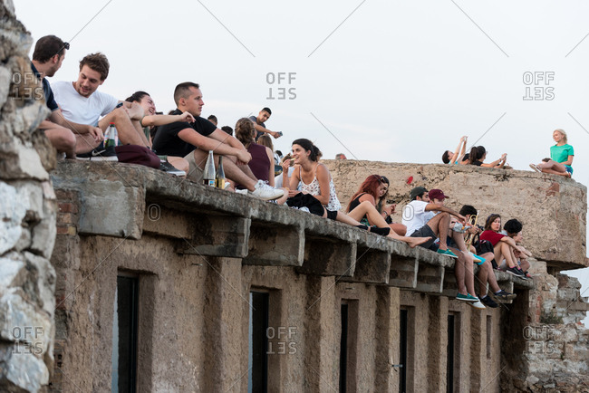 Barcelona, Spain - June 20, 2017: Friends sitting on a balcony with landscape
