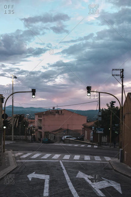 Sardinia, Italy - June 15, 2017: Intersection with traffic lights in old town under sunset sky