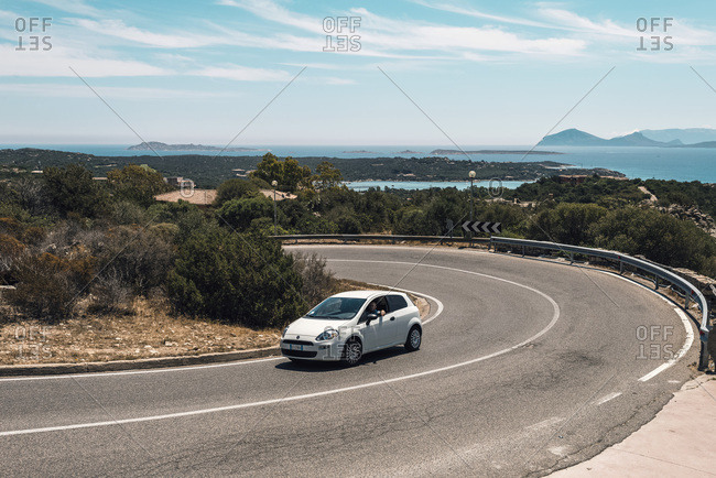 Sardinia, Italy - June 15, 2017: Car driving uphill on winding road in summer