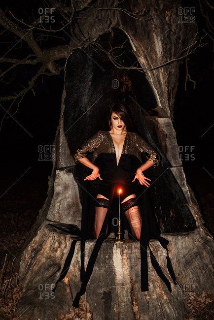 Woman in a black dress kneeling on a tree stump behind a lit candle