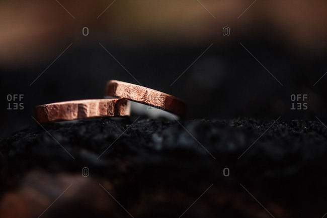 Two copper wedding bands leaning against each other on a dark surface