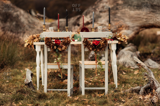 Outdoor woodland table decorated with candles and garlands of fallen leaves