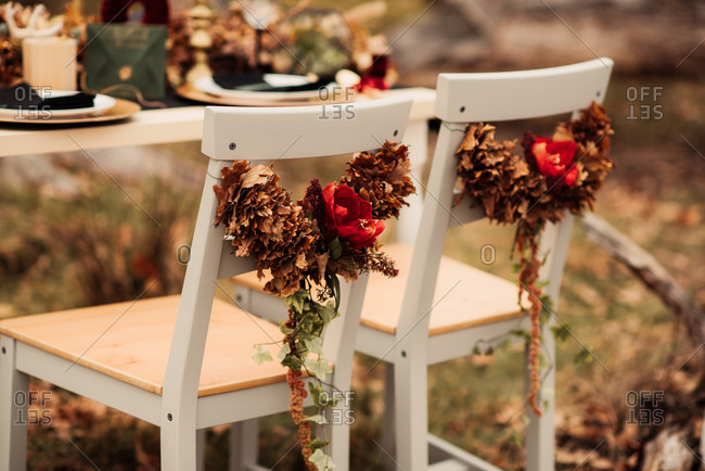 Chairs at a woodland reception decorated with garlands of autumn leaves