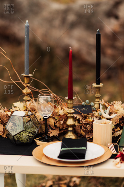 Dining table decorated with autumn leaves and candlesticks