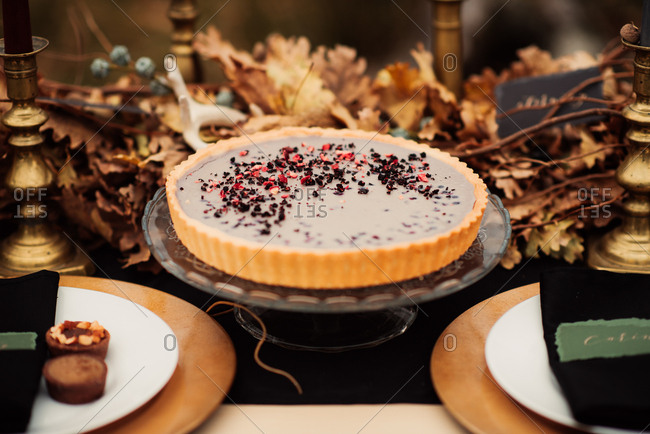 Pie with chopped fruit and chocolate on a table decorated with autumn leaves