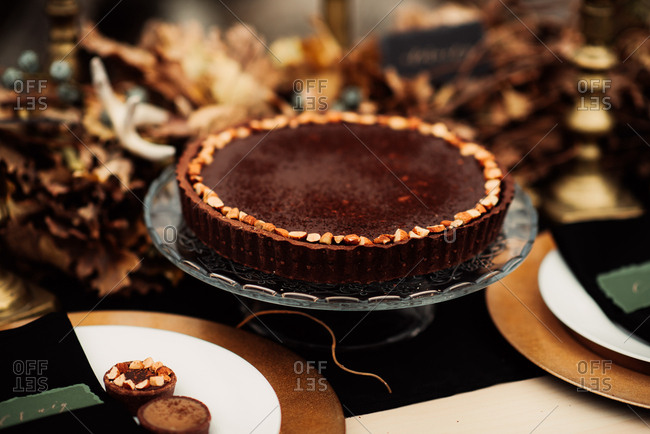 Chocolate cake on a rustic dessert table decorated with autumn leaves
