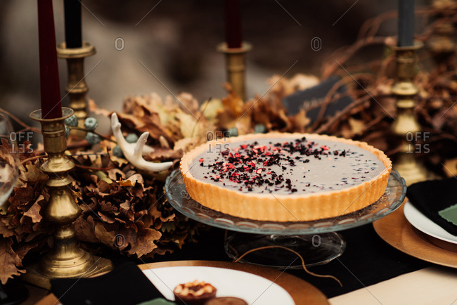 Pie on a dessert stand on a table decorated with autumn leaves