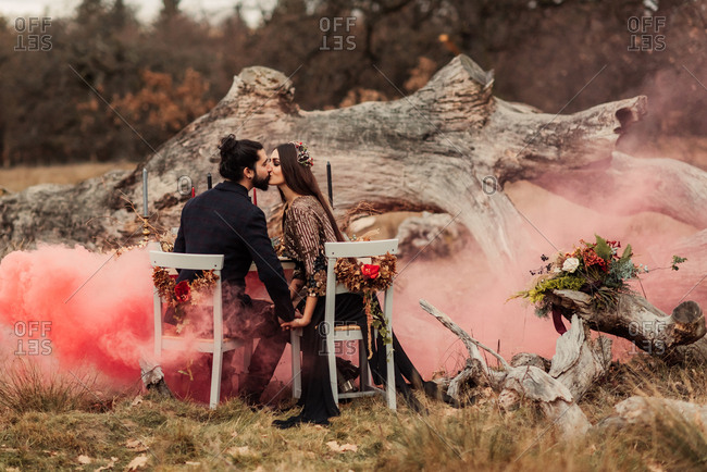 Newlyweds kissing at a reception table in a field with pink smoke
