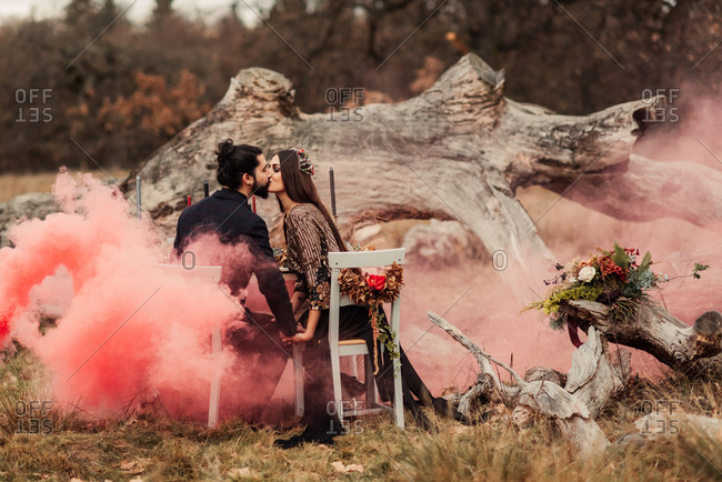 Newlywed couple holding hands and kissing at a table in a field with pink smoke