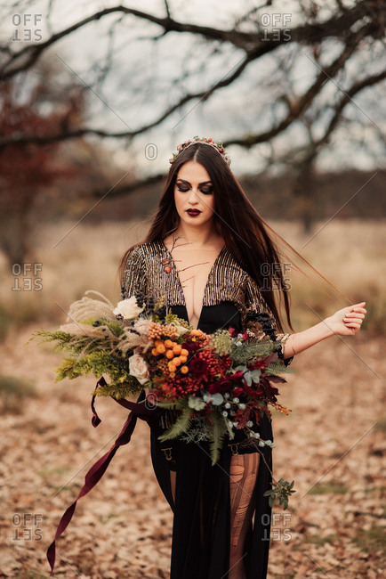 Bride in an elegant black gown holding a bouquet of woodland flowers