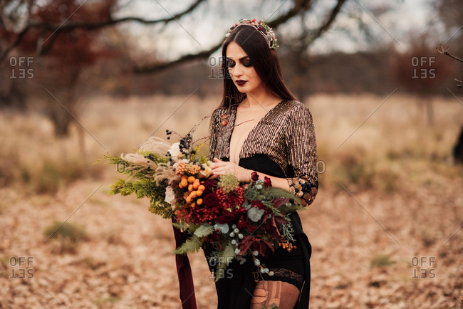 Bride in a black dress and flower crown holding a bouquet of woodland flowers