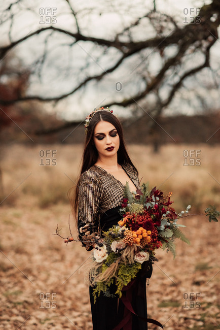 Bride standing in a field holding a bouquet of woodland flowers