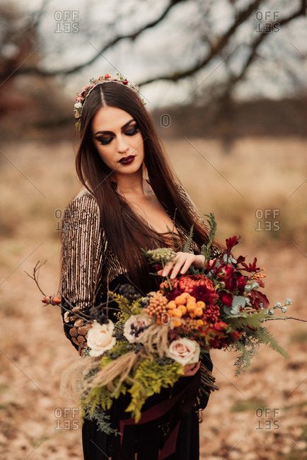 Bride in an autumn field holding a bouquet of woodland flowers