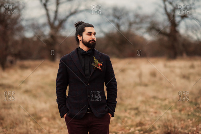 Groom in a plaid suit jacket standing in a remote field
