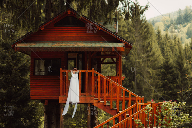 Bridal gown hanging from cabin porch