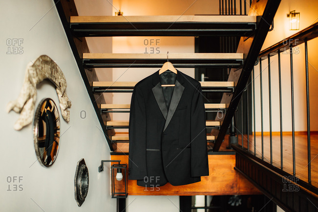 Groom's tuxedo jacket hanging from staircase