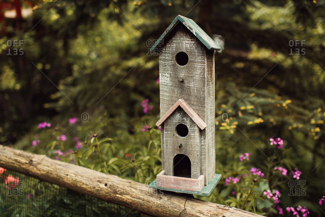 Rustic birdhouse on top of fence railing