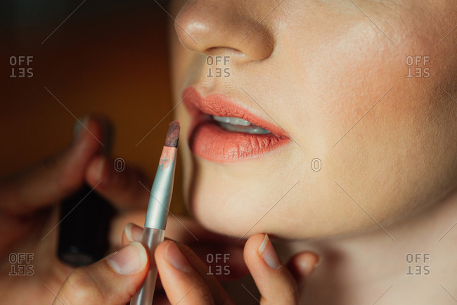 Bride having makeup applied to her lips for a wedding