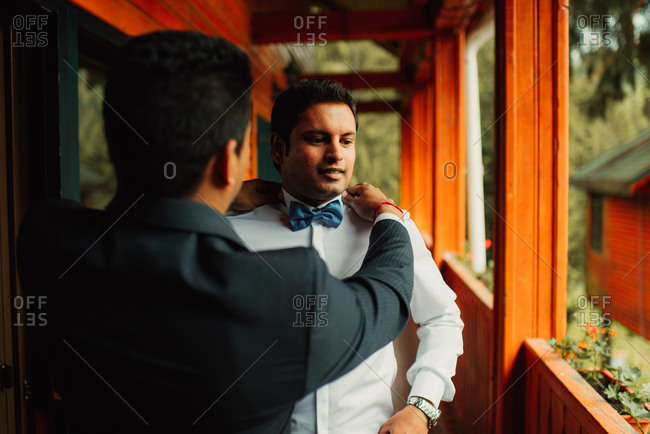 Groomsman helping groom get ready for his wedding