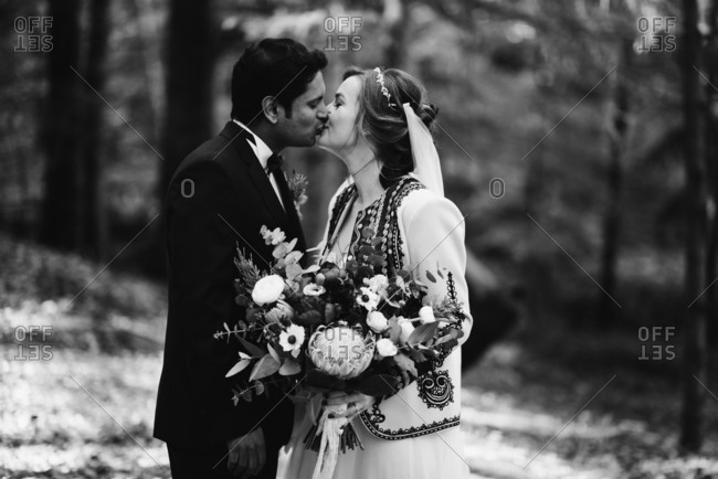 Bride and groom kissing in the forest in black and white