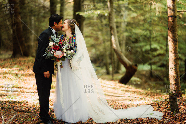 Happy bride and groom kissing in the woods