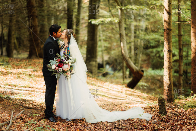 Newlywed couple kissing in the woods