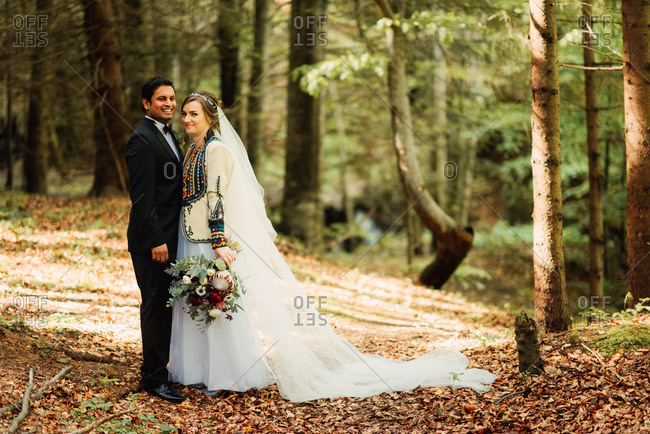 Happy bride and groom standing together in the woods