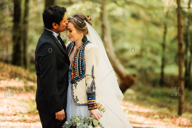 Groom kissing his bride's forehead in the woods
