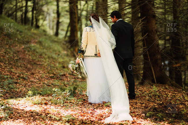 Bride and groom walking together in the woods