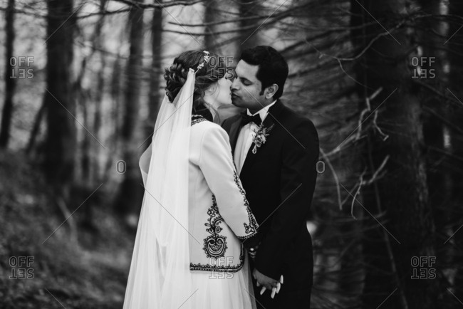 Bride and groom kissing in the woods in black and white