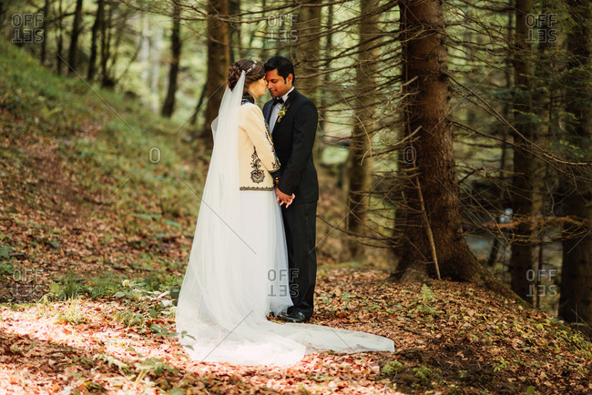 Bride and groom embraced in the forest