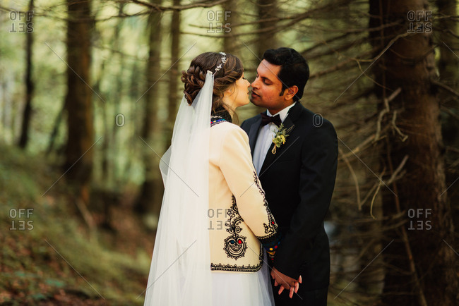 Newlywed couple holding hands and kissing in the forest