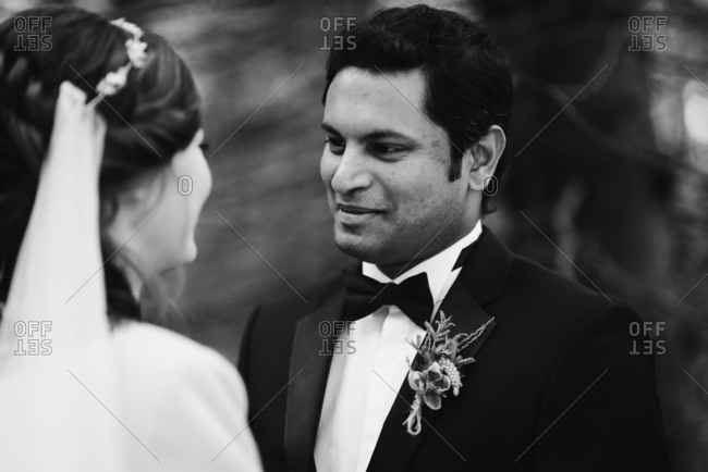 Groom looking into his bride's eyes in black and white