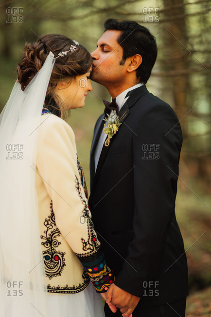 Groom kissing his bride's forehead in the forest